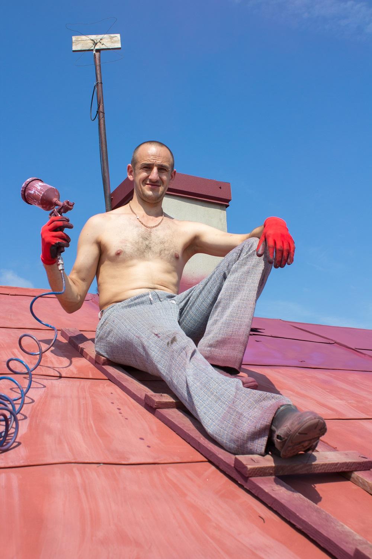 Malarz na dachu maluje natryskowo